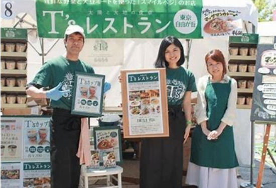 A happy family stands in front of their booth at Japan's Veg Festival. The booth has samples and posters about their products.
