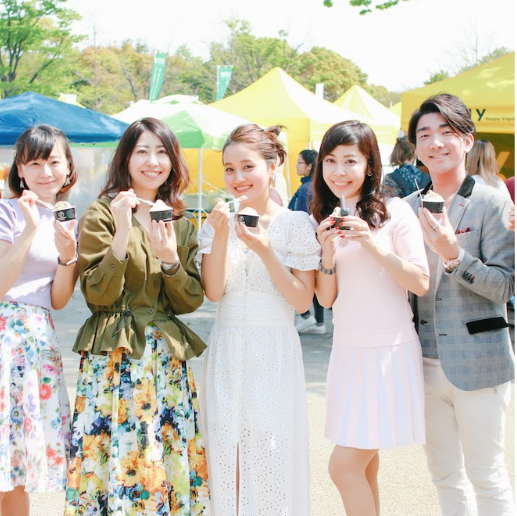 Photo taken of a group of 5 at Japan's Veg Festival. The whole group is happy, smiling at the camera, holding a small vegan ice cream.