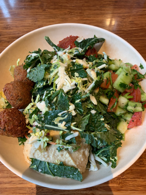 A vegan dish from Veggie Grill. The dish has spring rolls, falafel, cucumbers and tomatoes, kale, a red sause, and vegan cheese shredded on top.