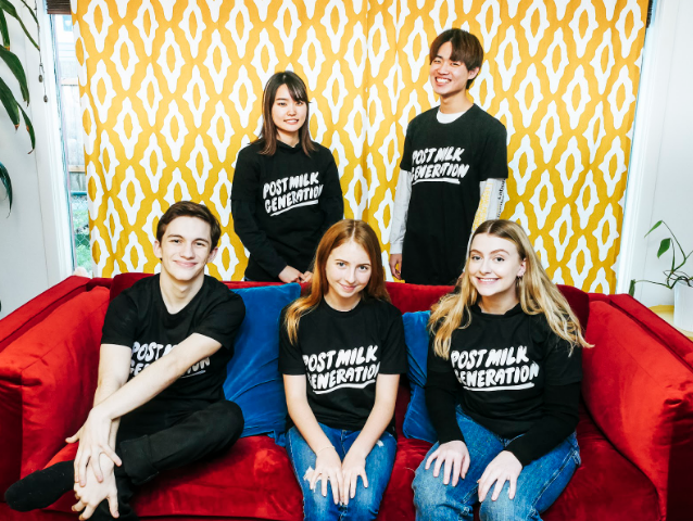 "Group photo of 5 Ravens, all happily sitting on a couch wearing a shirt that reads ""Post Milk Generation."""