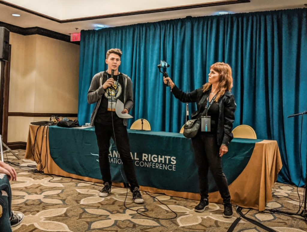 A Raven speaking into a microphone at a panel at the Animal Rights National Conference. A staff member is recording him with a camera.
