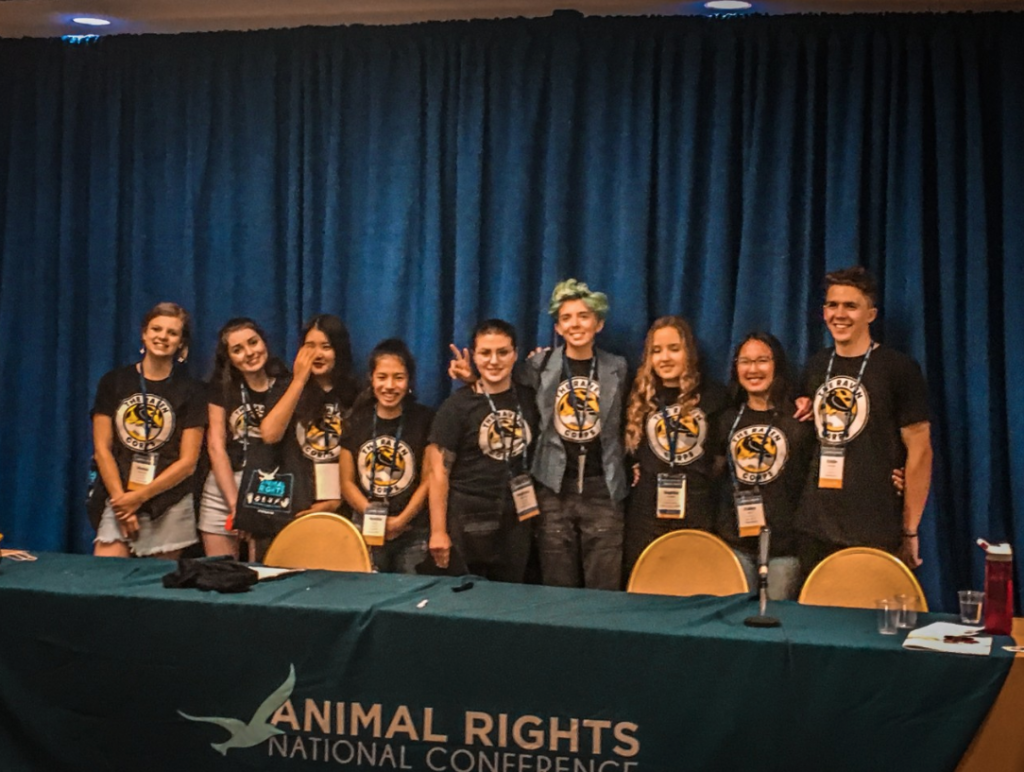9 Ravens posing for a photo behind the panel tabel. They are all smiling for the camera and wearing their The Raven Corps t-shirts.