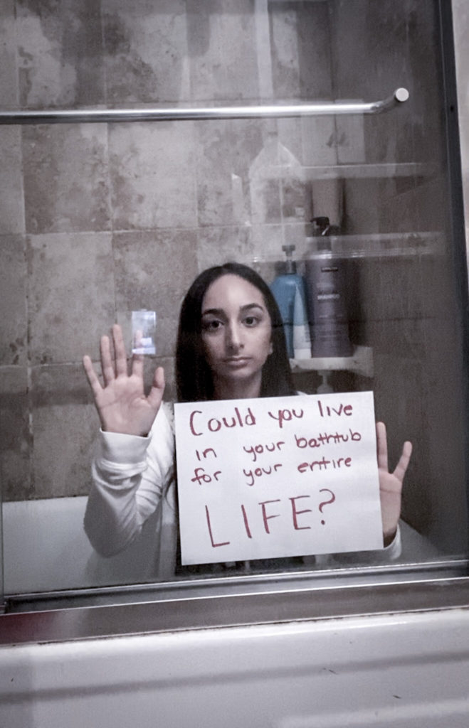 """Erin sitting in a bathtub with the glass door closed. She has a neutral expression and is holding her hands up to the glass with a sign that reads """"Could you live in your bathtub for your entire life?"""""""