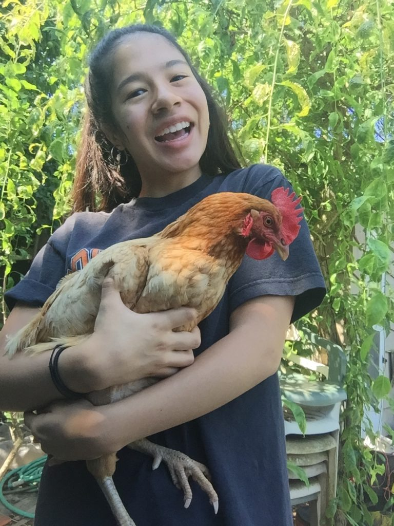 Jennifer standing outside holding a tan chicken with a big smile.