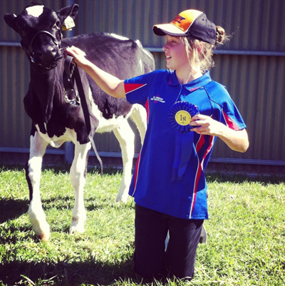Young Sophia holding the harness of a young black-and-white cow, showing off her 1st prize ribbon.